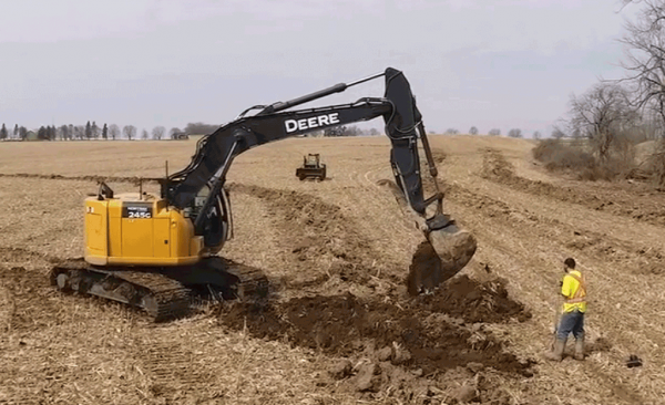 Excavator laying drainage tile