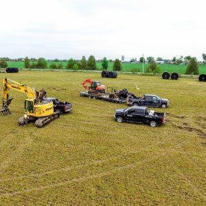 Multiple trucks in field for tiling