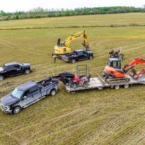 Multiple vehicles set up in field for tiling